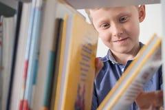 Το χαριτωμένο μικρό παιδί επιλέγει ένα βιβλίο στο ράφι στοκ φωτογραφίες