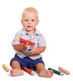 Το χαριτωμένο μικρό παιδί κάθεται και κρατά τα μεγάλα μολύβια απομονωμένα Στοκ Φωτογραφία