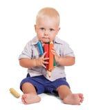 Το χαριτωμένο μικρό παιδί κάθεται και κρατά τα μολύβια μερών απομονωμένα Στοκ εικόνα με δικαίωμα ελεύθερης χρήσης