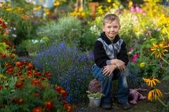 Το χαριτωμένο μικρό παιδί κάθεται στον κήπο λουλουδιών Φύση Στοκ φωτογραφία με δικαίωμα ελεύθερης χρήσης