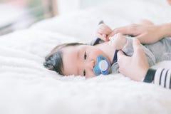 Το χαριτωμένο μωρό απορροφά τον ειρηνιστή και κοιμάται σε έναν μαλακό άσπρο τάπητα Το καλό μωρό ξαπλώνει σε έναν μαλακό άσπρο τάπ στοκ εικόνα