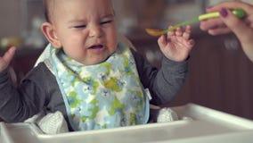 Το χαριτωμένο μωρό δεν θέλει να φάει τα χαϊδεμένα στερεά προβλήματος μητέρων τροφίμων της σε αργή κίνηση απόθεμα βίντεο