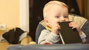 Το χαριτωμένο μωρό μηνών 9-10 δαγκώνει και δοκιμάζει το βιβλίο απόθεμα βίντεο