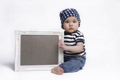 Το χαριτωμένο μωρό που κρατά ένα κενό πλαισίωσε το σημάδι Στοκ φωτογραφίες με δικαίωμα ελεύθερης χρήσης