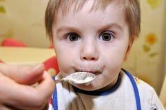 Το χαριτωμένο μωρό τρώει το κουάκερ στοκ εικόνες