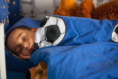 Το χαριτωμένο νέο αγόρι κοιμάται με taddy στο κρεβάτι του Στοκ φωτογραφία με δικαίωμα ελεύθερης χρήσης