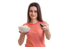 Το χαριτωμένο νέο κορίτσι κοιτάζει προς τα εμπρός και κρατά το μακρινό και το πιάτο με pop-corn Στοκ Εικόνα