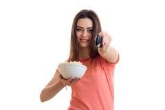 Το χαριτωμένο νέο κορίτσι με pop-corn τέντωσε εμπρός το χέρι της και αλλάζει τον τηλεχειρισμό καναλιών Στοκ Εικόνες