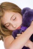Το χαριτωμένο νέο κορίτσι που αγκαλιάζει πορφυρό έναν teddy αντέχει Στοκ φωτογραφία με δικαίωμα ελεύθερης χρήσης