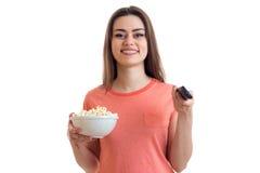 Το χαριτωμένο νέο κορίτσι προσέχει μια TV και τρώει pop-corn Στοκ εικόνα με δικαίωμα ελεύθερης χρήσης