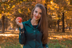 Το χαριτωμένο νέο κορίτσι στις σκοτεινές στάσεις ενδυμάτων στο πάρκο κρατά τη Apple στο χέρι του και χαμογελά Στοκ Φωτογραφία