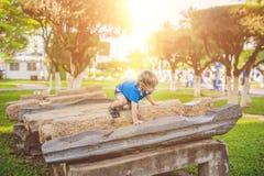 Το χαριτωμένο ξανθό αγόρι αναρριχείται επάνω στους φραγμούς πετρών στην παιδική χαρά Παιδική ηλικία, έννοια Στοκ φωτογραφίες με δικαίωμα ελεύθερης χρήσης