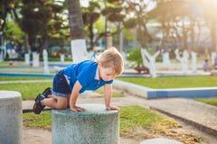 Το χαριτωμένο ξανθό αγόρι αναρριχείται επάνω στους φραγμούς πετρών στην παιδική χαρά Παιδική ηλικία, έννοια Στοκ Εικόνες