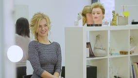 Το χαριτωμένο ξανθό κορίτσι εξετάζει στον καθρέφτη το σαλόνι ομορφιάς απόθεμα βίντεο