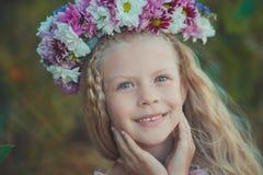 Το χαριτωμένο ξανθό κορίτσι με τα μπλε μάτια κλείνει το πορτρέτο φορώντας το άγριο στεφάνι λουλουδιών στο τοπ κεφάλι που χαμογελά Στοκ εικόνα με δικαίωμα ελεύθερης χρήσης