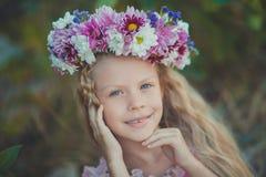 Το χαριτωμένο ξανθό κορίτσι με τα μπλε μάτια κλείνει το πορτρέτο φορώντας το άγριο στεφάνι λουλουδιών στο τοπ κεφάλι που χαμογελά Στοκ φωτογραφία με δικαίωμα ελεύθερης χρήσης