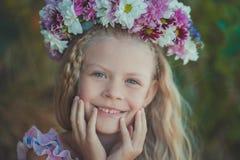 Το χαριτωμένο ξανθό κορίτσι με τα μπλε μάτια κλείνει το πορτρέτο φορώντας το άγριο στεφάνι λουλουδιών στο τοπ κεφάλι που χαμογελά Στοκ Εικόνες