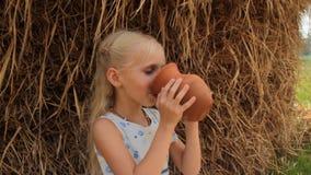 Το χαριτωμένο ξανθό κορίτσι πίνει το φρέσκο γάλα αγελάδων ` s από μια κανάτα αργίλου ενάντια στη θυμωνιά χόρτου το καλοκαίρι στο  απόθεμα βίντεο