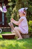 Το χαριτωμένο ξανθό κορίτσι παιδιών παίζει το πλύσιμο παιχνιδιών στο θερινό κήπο Στοκ εικόνες με δικαίωμα ελεύθερης χρήσης