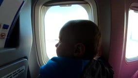 Το χαριτωμένο ξανθό μικρό παιδί κάθεται κοντά στο παράθυρο αεροπλάνων απόθεμα βίντεο