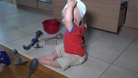 Το χαριτωμένο παιδί με να κάνει καπέλων αρχιμαγείρων βρωμίζει στην κουζίνα Παιχνίδι αγοριών μικρών παιδιών στο πάτωμα απόθεμα βίντεο