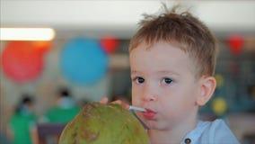 Το χαριτωμένο παιδί πίνει μια γούρνα καρύδων ένα άχυρο, κινηματογράφηση σε πρώτο πλάνο Έννοια: παιδιά, ευτυχής παιδική ηλικία, κα απόθεμα βίντεο