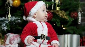 Το χαριτωμένο παιχνίδι αγοριών κοντά στο χριστουγεννιάτικο δέντρο, λίγο μωρό έντυσε στις εξαρτήσεις Santa, παιδί στα παιχνίδια κο φιλμ μικρού μήκους