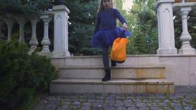 Το χαριτωμένο περπάτημα κοριτσιών με το τέχνασμα ή μεταχειρίζεται την τσάντα που πηγαίνει στο γείτονα για τις καραμέλες, διακοπές φιλμ μικρού μήκους