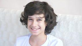 Το χαριτωμένο σγουρός-μαλλιαρό αγόρι ο έφηβος εξετάζει τη κάμερα γελώντας και κάνει μια αστεία έκφραση του προσώπου r απόθεμα βίντεο