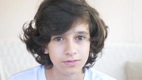 Το χαριτωμένο σγουρός-μαλλιαρό αγόρι ο έφηβος εξετάζει τη κάμερα γελώντας και κάνει μια αστεία έκφραση του προσώπου r φιλμ μικρού μήκους