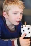 Το χαριτωμένο σχολικό αγόρι πίνει milkshake Στοκ Φωτογραφίες