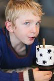 Το χαριτωμένο σχολικό αγόρι πίνει milkshake Στοκ φωτογραφία με δικαίωμα ελεύθερης χρήσης