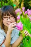 Το χαριτωμένο ταϊλανδικό κορίτσι είναι πολύ ευχαριστημένο από τα ζωηρόχρωμα λουλούδια Στοκ Φωτογραφίες