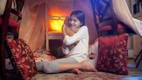 Το χαριτωμένο χαμογελώντας κορίτσι στις πυτζάμες που κάθονται στο πάτωμα τη νύχτα και το αγκάλιασμα teddy αντέχουν Στοκ Εικόνες