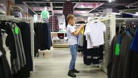 Το χαριτωμένο χαμογελώντας αγόρι στέκεται κοντά στα ενδύματα και την επιλογή απόθεμα βίντεο