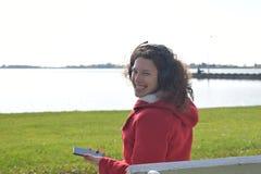 Το χαριτωμένο χαμογελώντας κορίτσι ακούει τη μουσική στα ακουστικά κοντά στη λίμνη Στοκ εικόνες με δικαίωμα ελεύθερης χρήσης