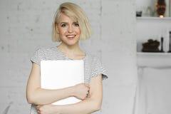 Το χαριτωμένο χαμόγελο νέων κοριτσιών και κρατά το lap-top στο φως της ημέρας Στοκ Εικόνα