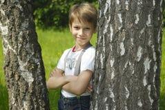 Το χαριτωμένο όμορφο αγόρι στέκεται επάνω στα δέντρα στοκ φωτογραφίες