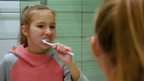 Το χαριτωμένο όμορφο κορίτσι κινηματογραφήσεων σε πρώτο πλάνο με τη δίκαιη τρίχα βουρτσίζει τα δόντια της λεπτομερώς στην αντανάκ