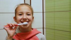 Το χαριτωμένο όμορφο κορίτσι κινηματογραφήσεων σε πρώτο πλάνο με τη δίκαιη τρίχα βουρτσίζει τα δόντια της λεπτομερώς και χαμογελά