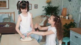 Το χαριτωμένο smudges κοριτσιών πρόσωπο αδελφών με το αλεύρι, έχει το χρόνο διασκέδασης στην κουζίνα, σε αργή κίνηση φιλμ μικρού μήκους