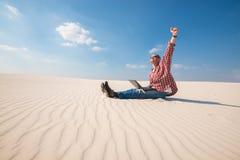 Το χαρούμενο άτομο με ένα lap-top κάθεται στην έρημο Στοκ εικόνες με δικαίωμα ελεύθερης χρήσης