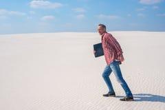 Το χαρούμενο άτομο περπατά μέσω της ερήμου με ένα lap-top στο εκτάριό του Στοκ Φωτογραφίες
