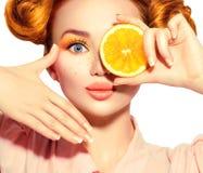 Το χαρούμενο έφηβη ομορφιάς παίρνει τα juicy πορτοκάλια Πρότυπο κορίτσι εφήβων με τις φακίδες, το αστείο κόκκινο hairstyle, το κί στοκ φωτογραφίες