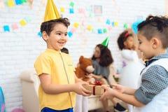 Το χαρούμενο αγόρι στο καπέλο γενεθλίων δίνει ένα δώρο σε λίγο αγόρι γενεθλίων χρόνος δώρων Στοκ φωτογραφία με δικαίωμα ελεύθερης χρήσης