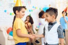 Το χαρούμενο αγόρι στο καπέλο γενεθλίων δίνει ένα δώρο σε λίγο αγόρι γενεθλίων χρόνος δώρων Στοκ Εικόνα