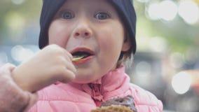 Το χαρούμενο και εύθυμο κορίτσι σε μια ΚΑΠ τρώει το παγωτό στενό στον επάνω προσώπου οδών φιλμ μικρού μήκους