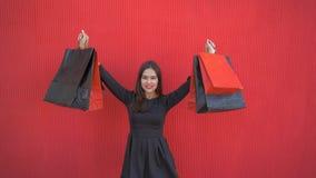 Το χαρούμενο κορίτσι αγοραστών ανυψώνει τις τσάντες αγορών επάνω και χορεύει από την ευτυχία στη μαύρη Παρασκευή της εποχιακής πώ απόθεμα βίντεο