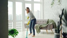 Το χαρούμενο κορίτσι το πάτωμα στο ελαφρύ διαμέρισμα και έχει τη διασκέδαση ακούοντας τη μουσική μέσω των ακουστικών, που χορεύου απόθεμα βίντεο