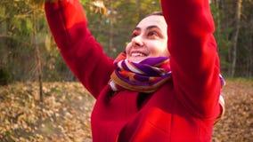 Το χαρούμενο κορίτσι ρίχνει τα φύλλα φιλμ μικρού μήκους